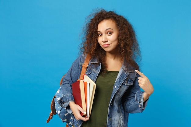 Joven estudiante triste en ropa de mezclilla y mochila tiene libros aislados en la pared azul