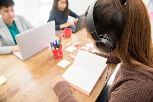 Joven estudiante universitaria con auriculares escuchando y leyendo el libro