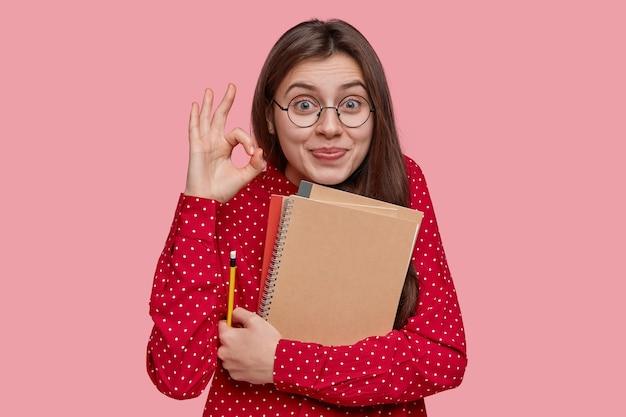 Joven estudiante universitaria morena demuestra que todo está bien, muestra un gesto correcto, sostiene blocs de notas y lápiz, confiado en el examen aprobado con éxito