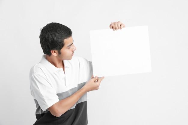 Joven estudiante universitario indio mostrando pizarra en la pared blanca
