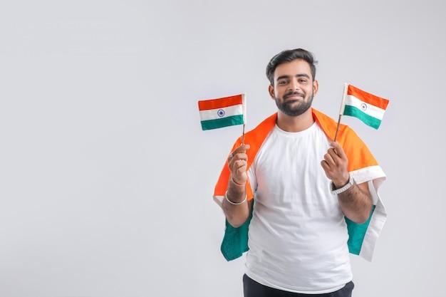 Joven estudiante universitario indio posando con bandera india.