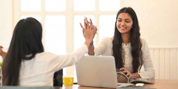 Joven estudiante universitario que da clases particulares con una computadora portátil mientras están sentados juntos en un escritorio de madera sobre una cómoda sala de estar