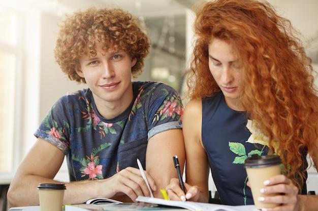 Joven estudiante universitario sentado cerca de su amiga pelirroja que lo está ayudando a estudiar