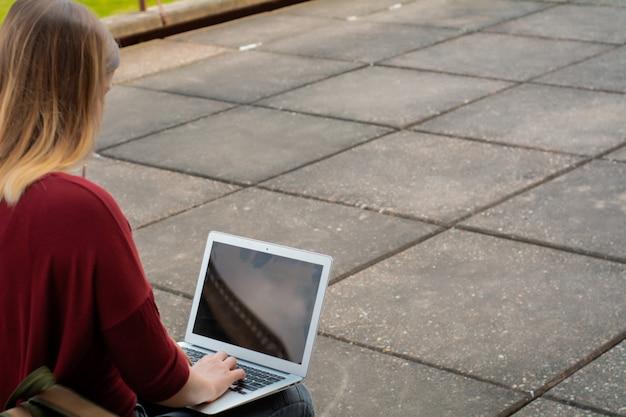 Joven estudiante usando laptop al aire libre.