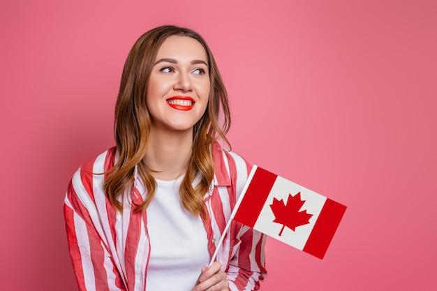 Joven estudiante vistiendo camisa a rayas rojas sonriendo y sosteniendo una pequeña bandera de canadá y mirando a otro lado aislado sobre espacio rosa, celebración del día de canadá