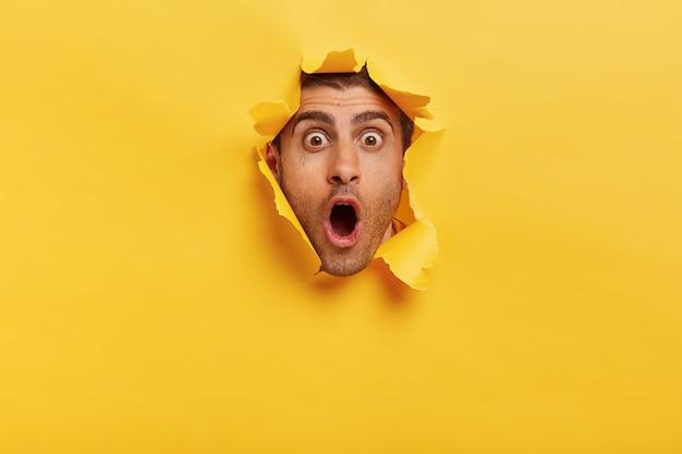 Un joven estupefacto con cerdas mantiene la mandíbula caída por la sorpresa, tiene los ojos abiertos