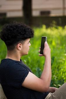 Joven étnico tomando foto en la calle