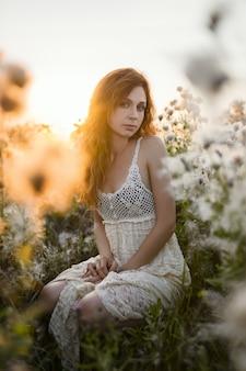 Joven europea en un campo con una corona de hierbas y un vestido blanco