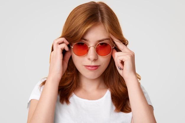Joven europea concentrada con expresión seria, mantiene las manos en las sienes, trata de concentrarse en algo, usa gafas de sol rojas y una camiseta blanca informal,