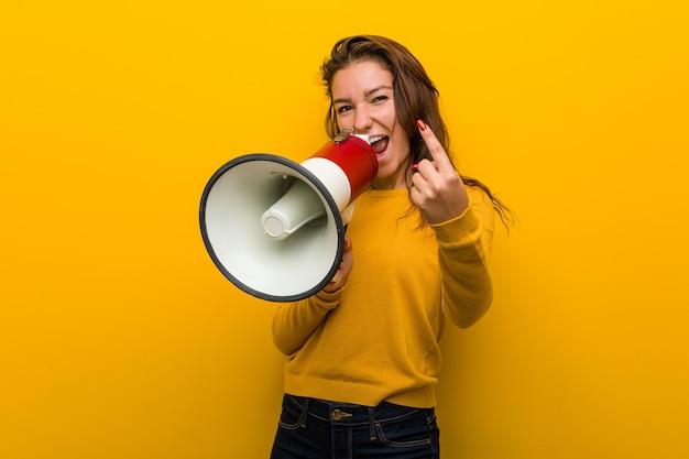 Joven europea sosteniendo un megáfono apuntando con el dedo como si invitara a acercarse.