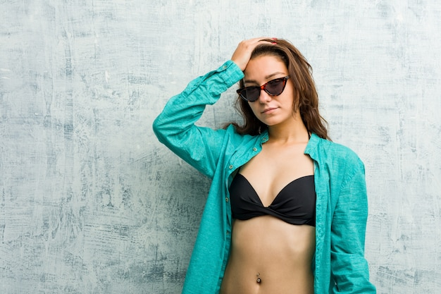 Joven europea vistiendo bikini olvidando algo, golpeándose la frente con la palma y cerrando los ojos.