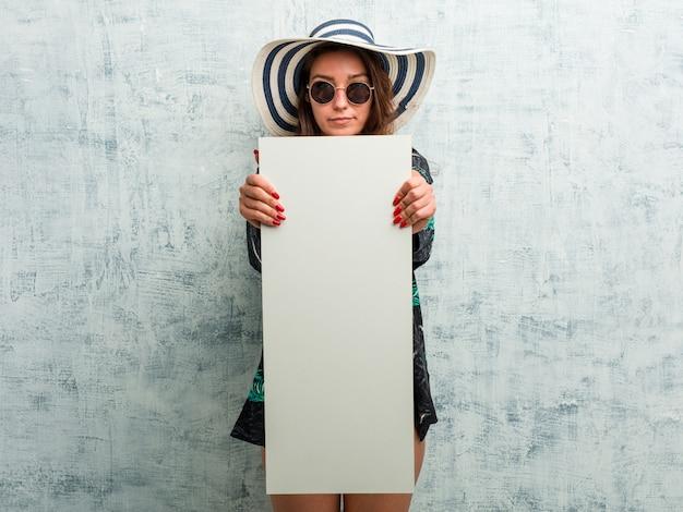 Joven europea vistiendo bikini y sosteniendo una pancarta