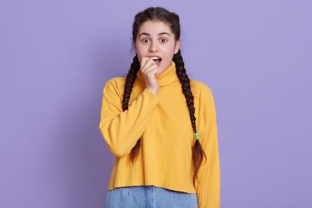 Joven excitada se muerde el puño con los ojos caídos, la dama se ve asombrada, con un suéter amarillo, posando