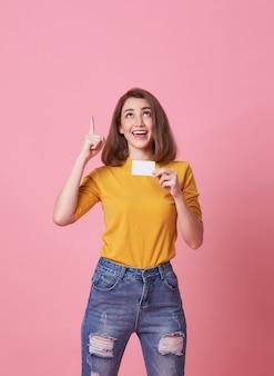 Joven excitada que muestra la tarjeta de crédito y punto de mano en el espacio de copia aislado sobre rosa.