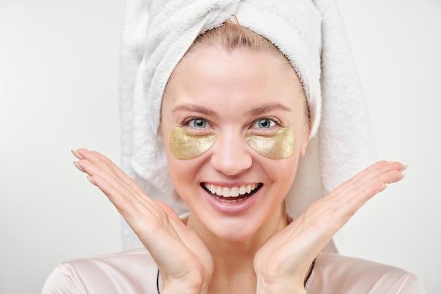 Joven excitada con revitalizantes parches dorados debajo de los ojos disfrutando del procedimiento de cuidado de la piel de forma aislada