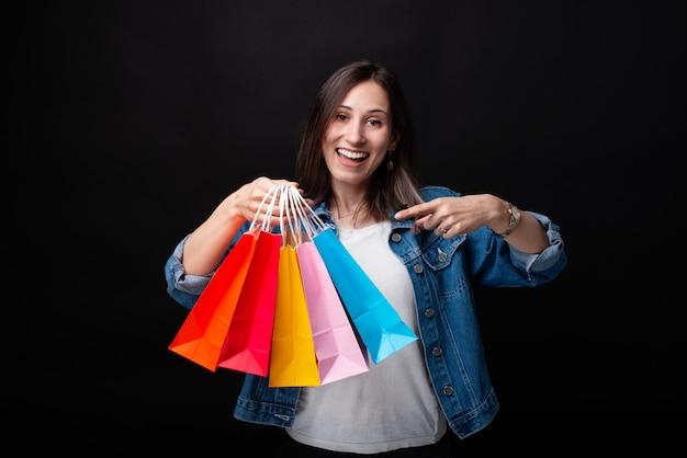 Joven excitada señalando coloridos bolsos de compras