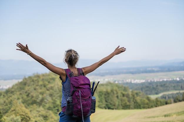 Joven excursionista disfrutando de la vida con los brazos en alto
