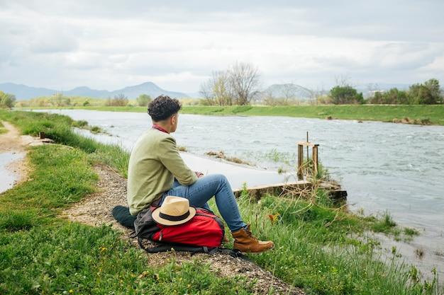 Joven excursionista emplazamiento cerca del hermoso río