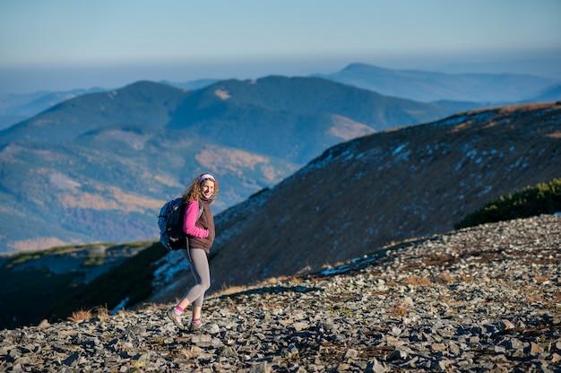 Joven excursionista feliz está caminando en la montaña plato