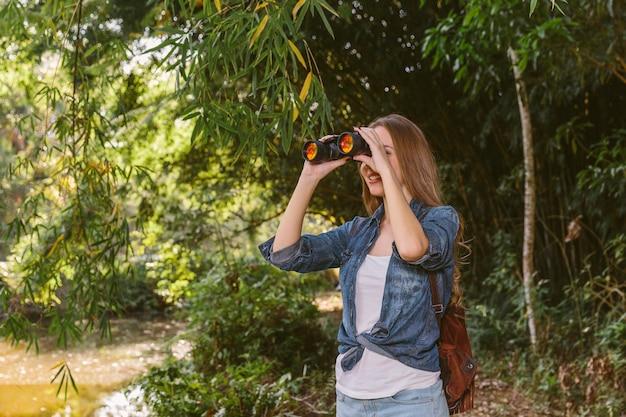 Joven excursionista mujer mirando a través de binoculares en el bosque