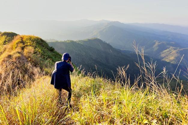 Joven excursionista tomando una fotografía a lo largo del camino de terkking. fotógrafo que toma la foto en el pico de la montaña.