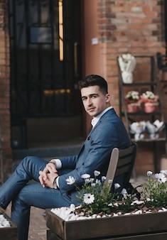 Joven exitoso vestido con un traje caro está sentado en la ciudad