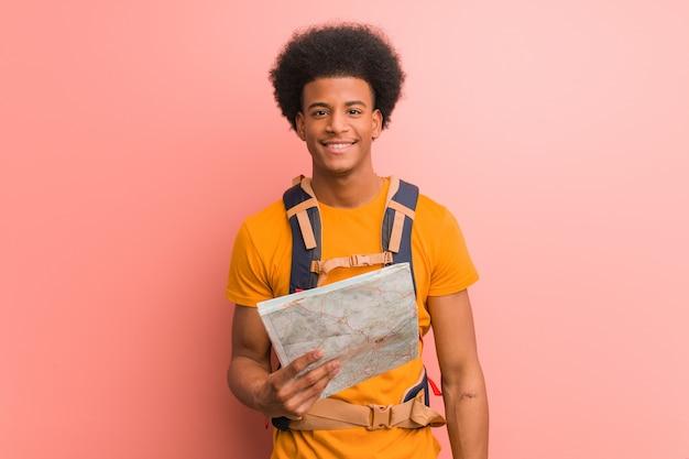 Joven explorador afroamericano hombre sosteniendo un mapa alegre con una gran sonrisa