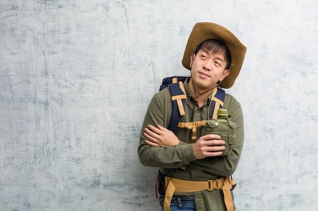 Joven explorador chino hombre sonriendo confiado y cruzando los brazos, mirando hacia arriba