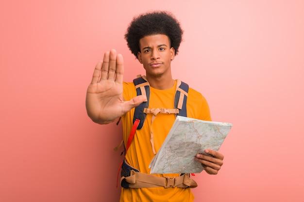 Joven explorador negro hombre sosteniendo un mapa poniendo la mano delante
