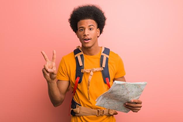 Joven explorador negro hombre sosteniendo un mapa que muestra el número dos
