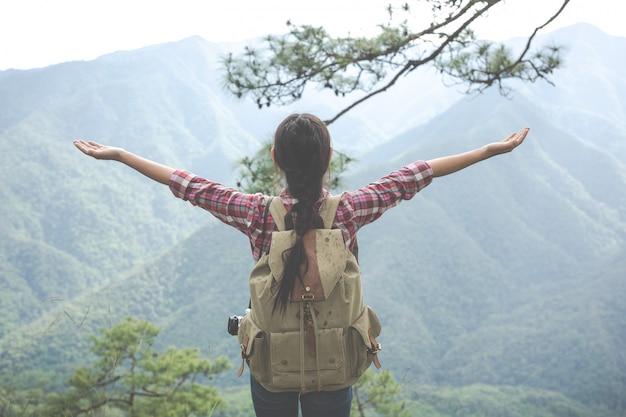 La joven extendió ambos brazos hasta la cima de la colina en un bosque tropical junto con mochilas en el bosque. aventura, senderismo.