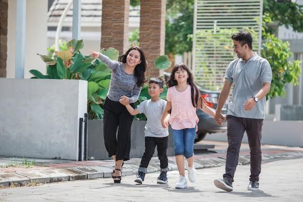Joven familia asiática feliz caminando juntos