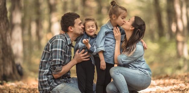 Una joven familia camina en el bosque de otoño con niños.