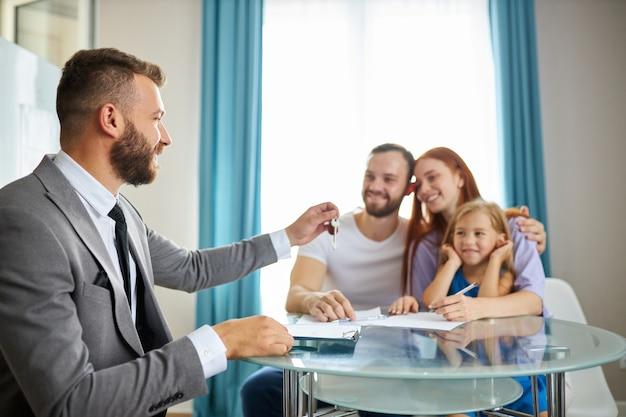 Joven familia caucásica con niño recibe llaves de su primer piso