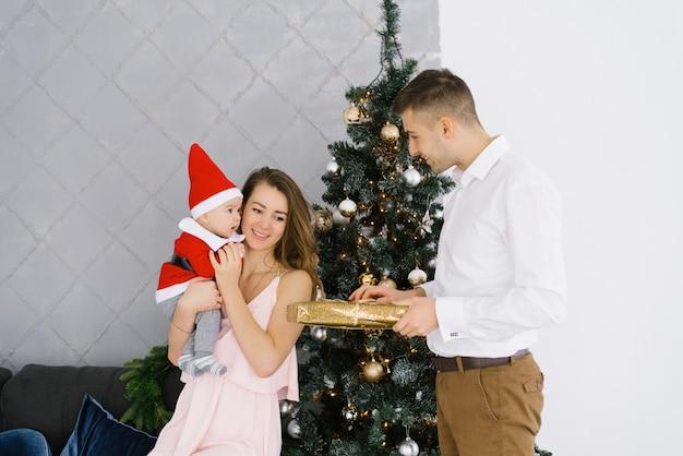 Una joven familia celebra la navidad en casa en la sala de estar cerca del árbol de navidad. feliz mamá, papá e hijo disfrutan de sus vacaciones juntos. el padre le da un regalo a la madre y al bebé