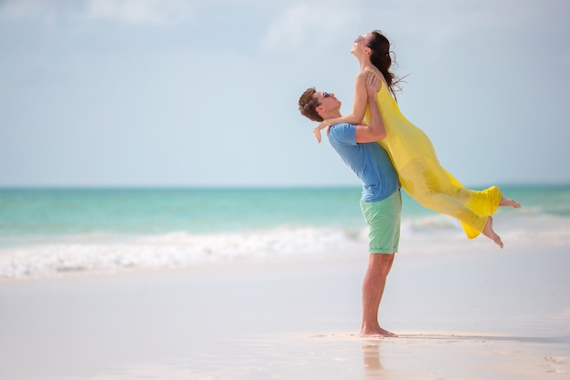 Joven familia de dos en la playa blanca durante las vacaciones de verano