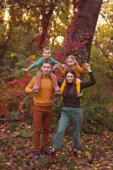 Joven familia feliz al aire libre en otoño