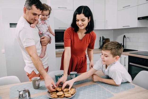 Joven familia feliz desayunando en la cocina de casa
