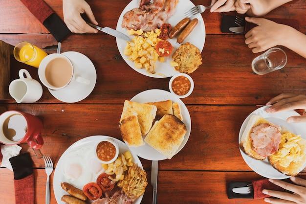Joven familia feliz desayunando