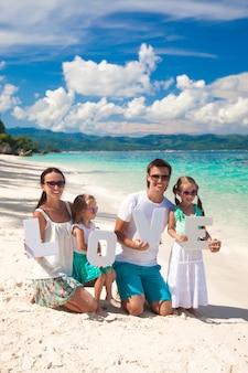 Joven familia feliz y dos niños con la palabra amor en vacaciones tropicales