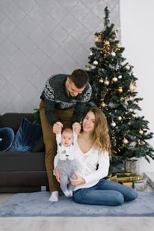Una joven familia feliz con un hijo pequeño se sienta en el suelo cerca de un árbol de navidad en la sala de estar. h