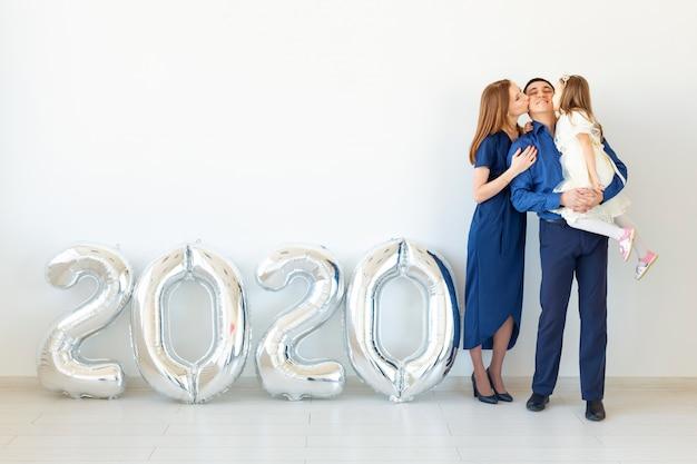 Joven familia feliz madre y padre e hija de pie cerca de globos con forma de números 2020. año nuevo