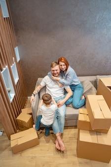 Joven familia feliz con niño desempacando cajas juntos sentados en el sofá