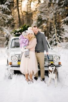 Una joven familia feliz con un niño pequeño se está preparando para la navidad, caminando con un perro husky en el fondo de un automóvil retro, en el techo de un árbol de navidad y regalos en el bosque nevado de invierno.