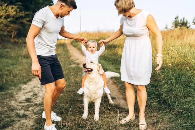 Joven familia feliz con perro divertirse al aire libre