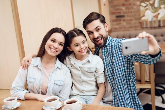 Joven familia feliz tomando selfie en la cafetería.