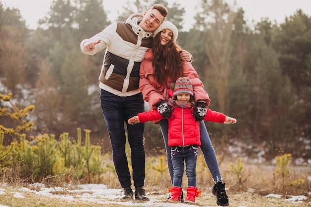 Joven familia juntos caminando en el bosque en invierno