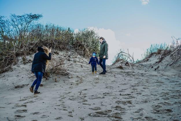 Una joven familia con niños pasa el fin de semana a orillas del frío mar báltico