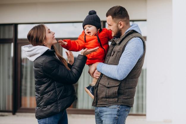 Joven familia con pequeño hijo junto a la casa