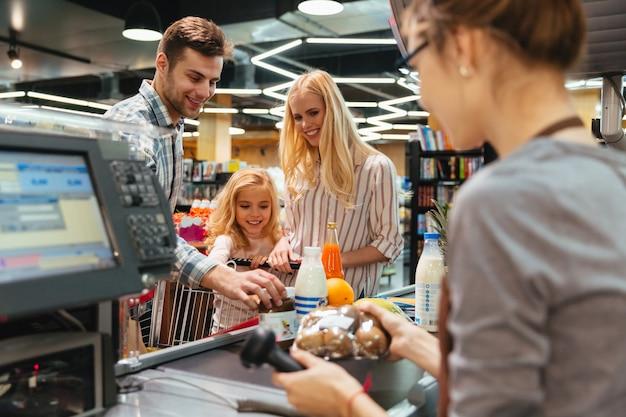 Joven familia de pie en el mostrador de efectivo